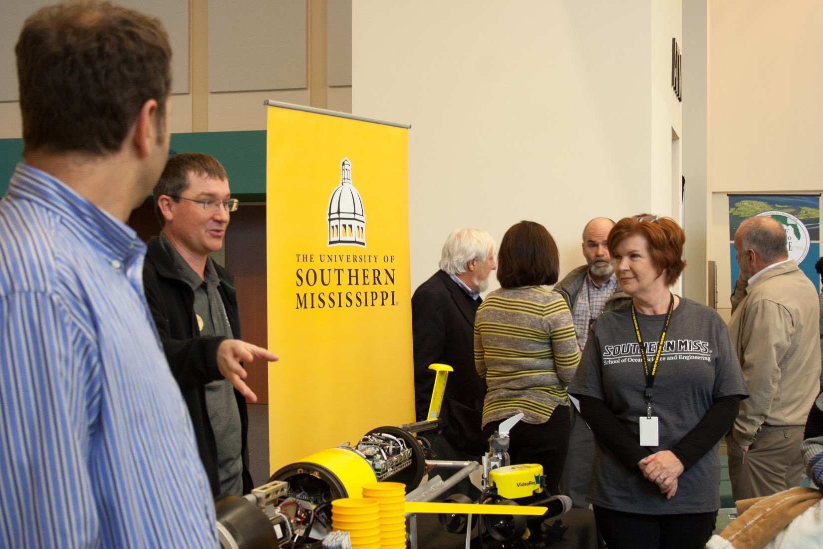 People gather around an exhibitor's booth, with an underwater remotely operated vehicle displayed on a table.