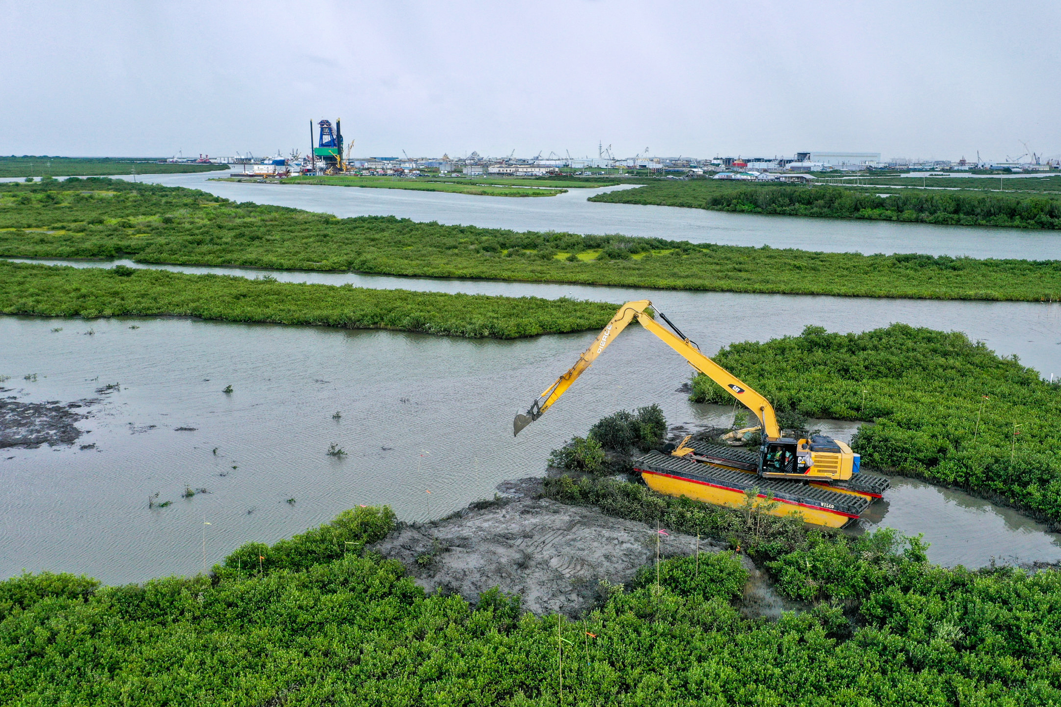 Aerial view of wetlands and marsh with a large excavator working among the landscape.