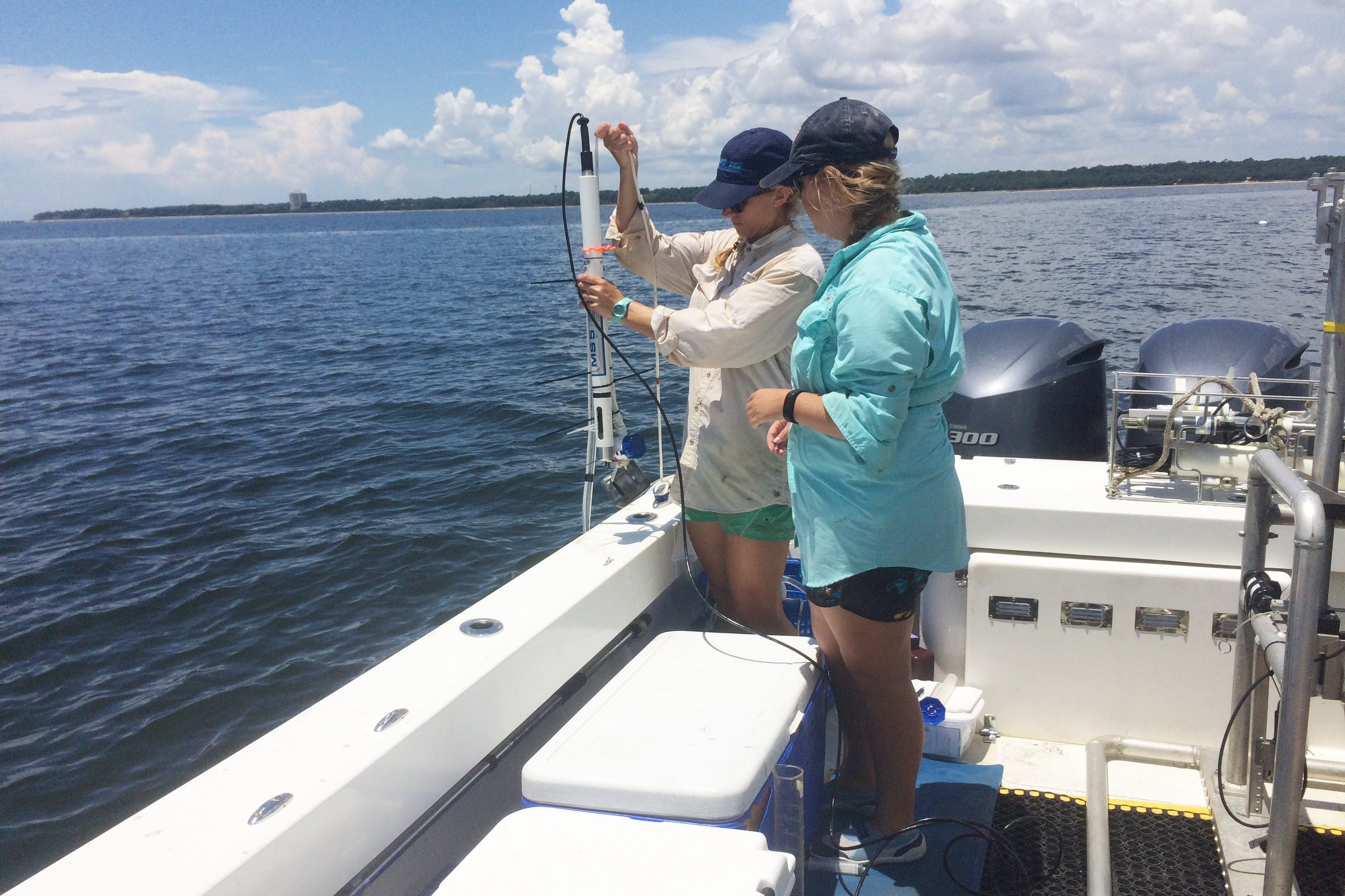 Two scientists on a boat hold a cylindrical monitoring device above the water.