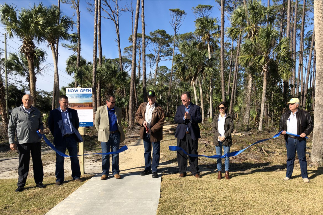 Agency officials and partners cut a ribbon to commemorate a project completion.