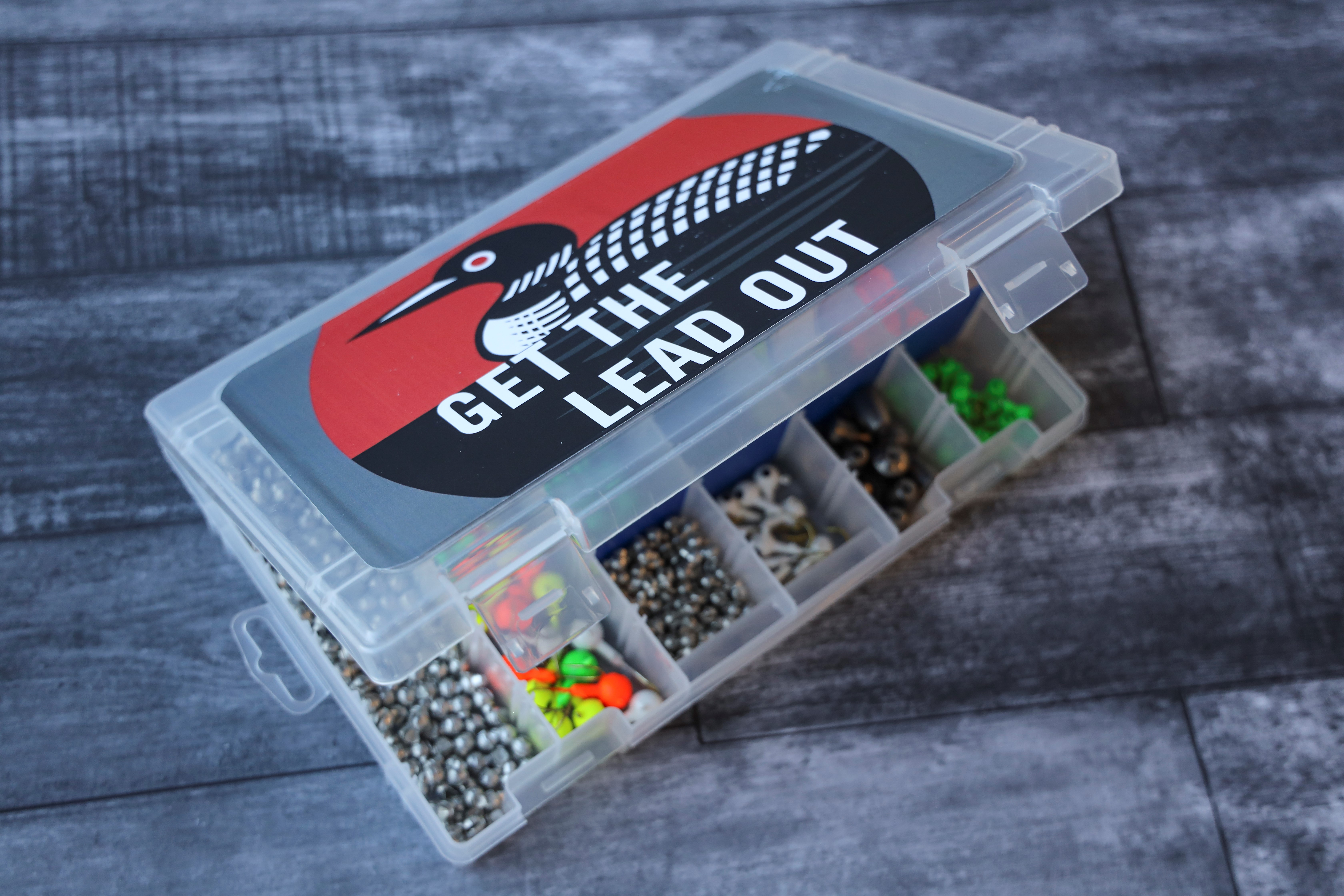"""A small fishing tackle box with a sticker that says """"Get the Lead Out."""""""