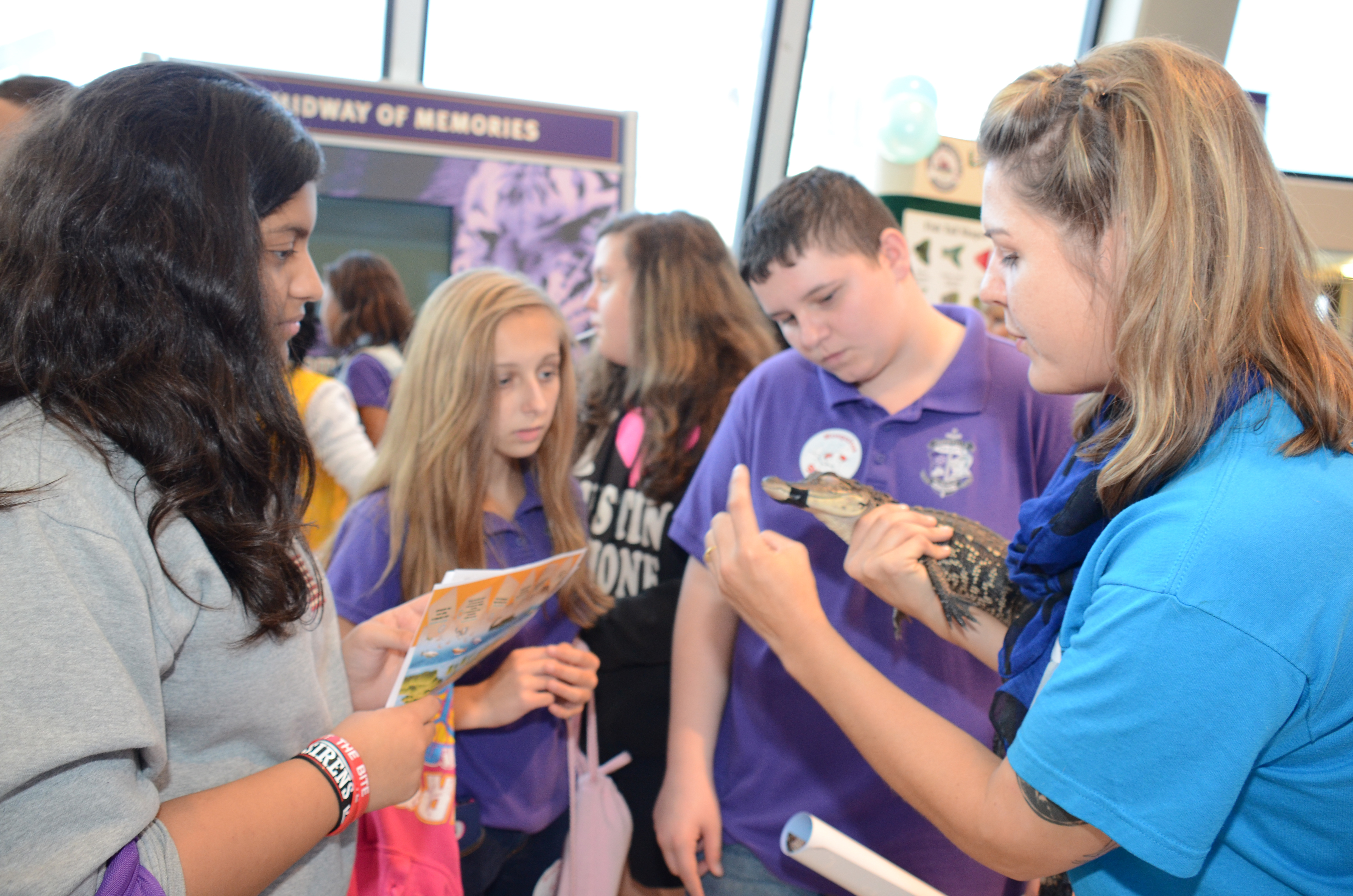 Children learn about wetlands while a science educator holds a juvenile alligator. Photo: Louisiana Sea Grant