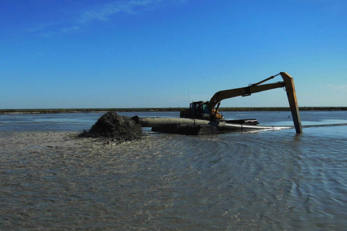 An excavator moves dredged sediment at a Louisiana marsh creation project. Image: CWPPRA