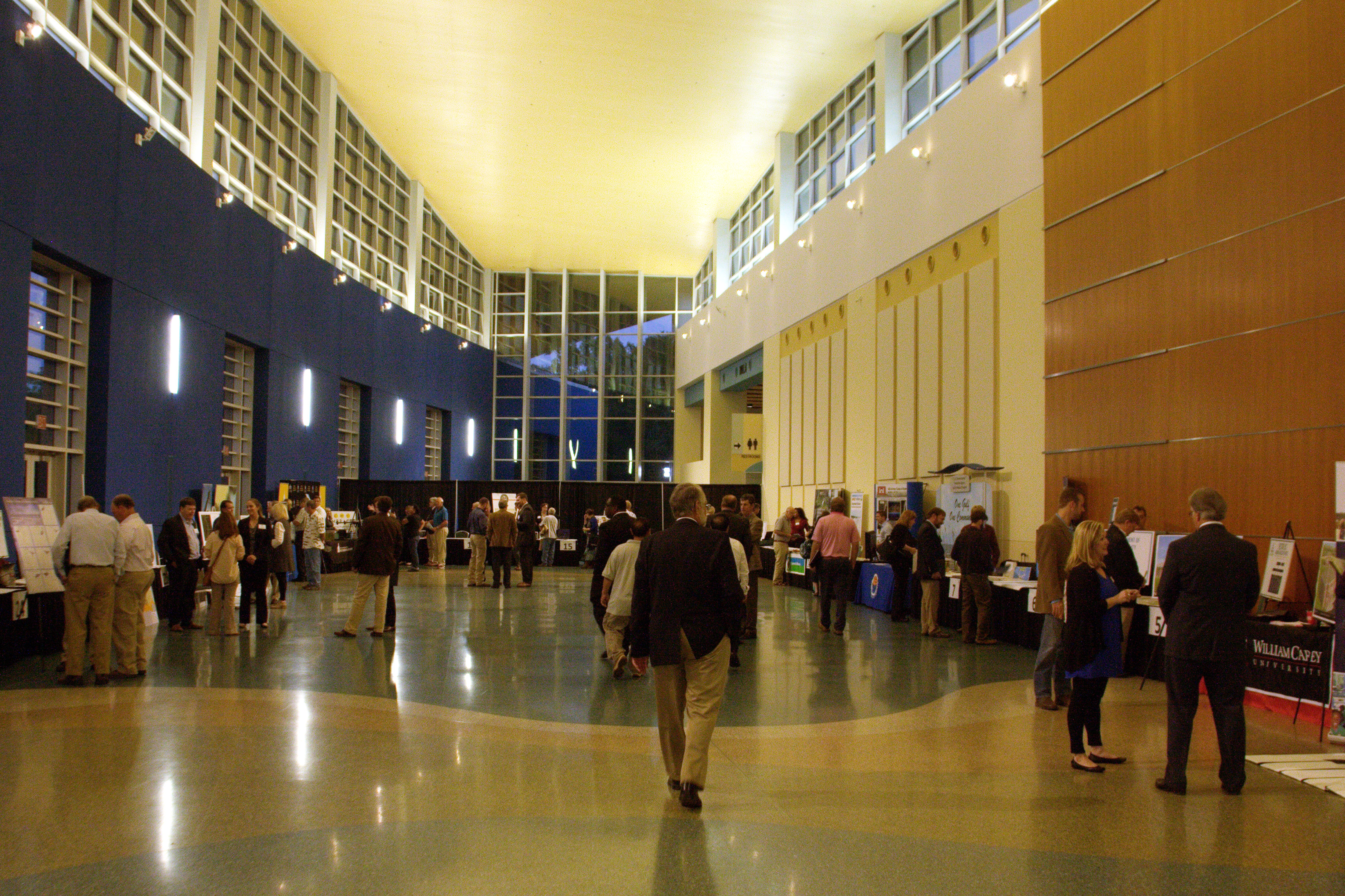 Exhibitors stand with other people at tables on both sides of a long hallway/atrium with high ceilings.