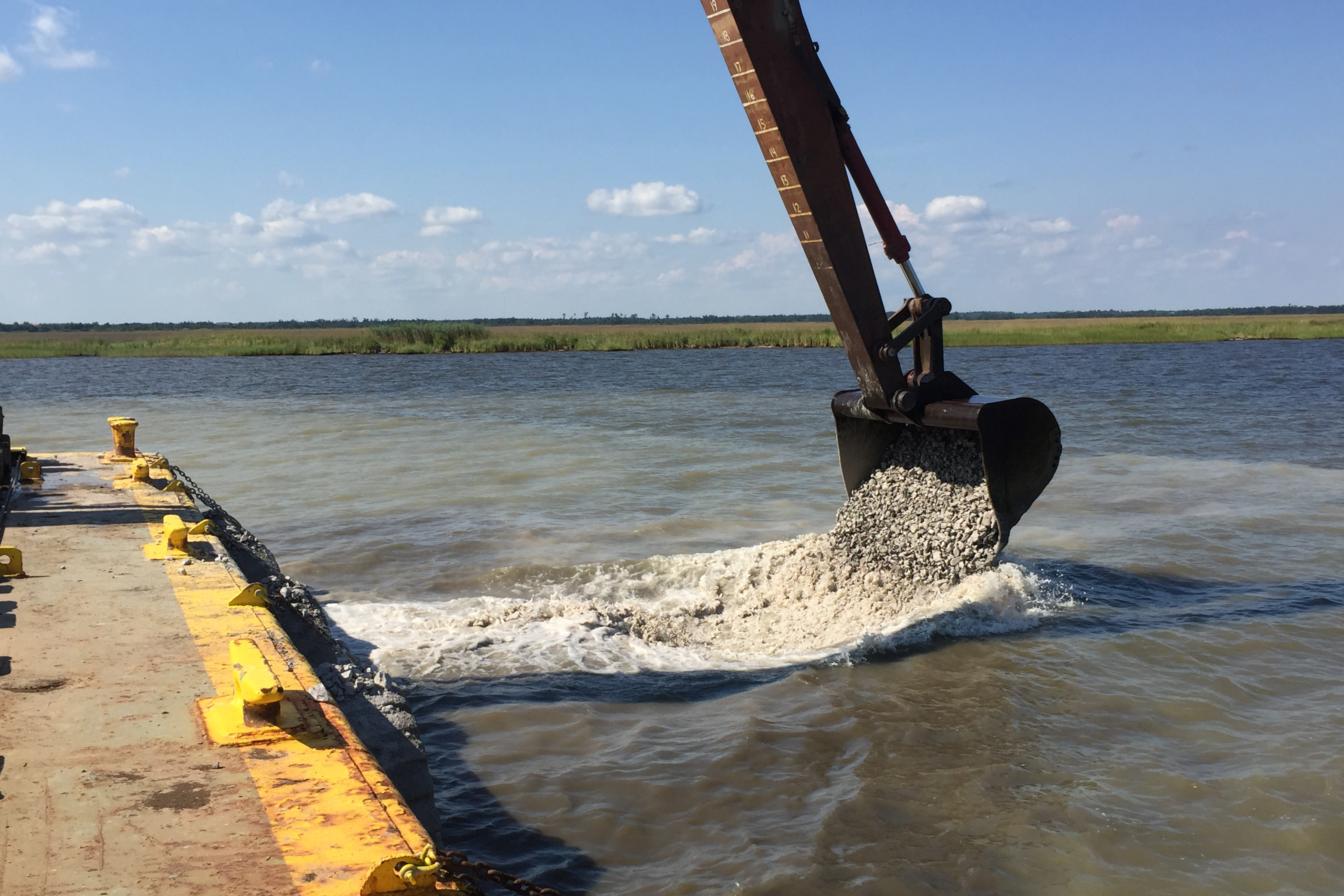 Excavator bucket distributing oyster cultch off of a barge. Photo: Covington Civil and Environmental, LLC