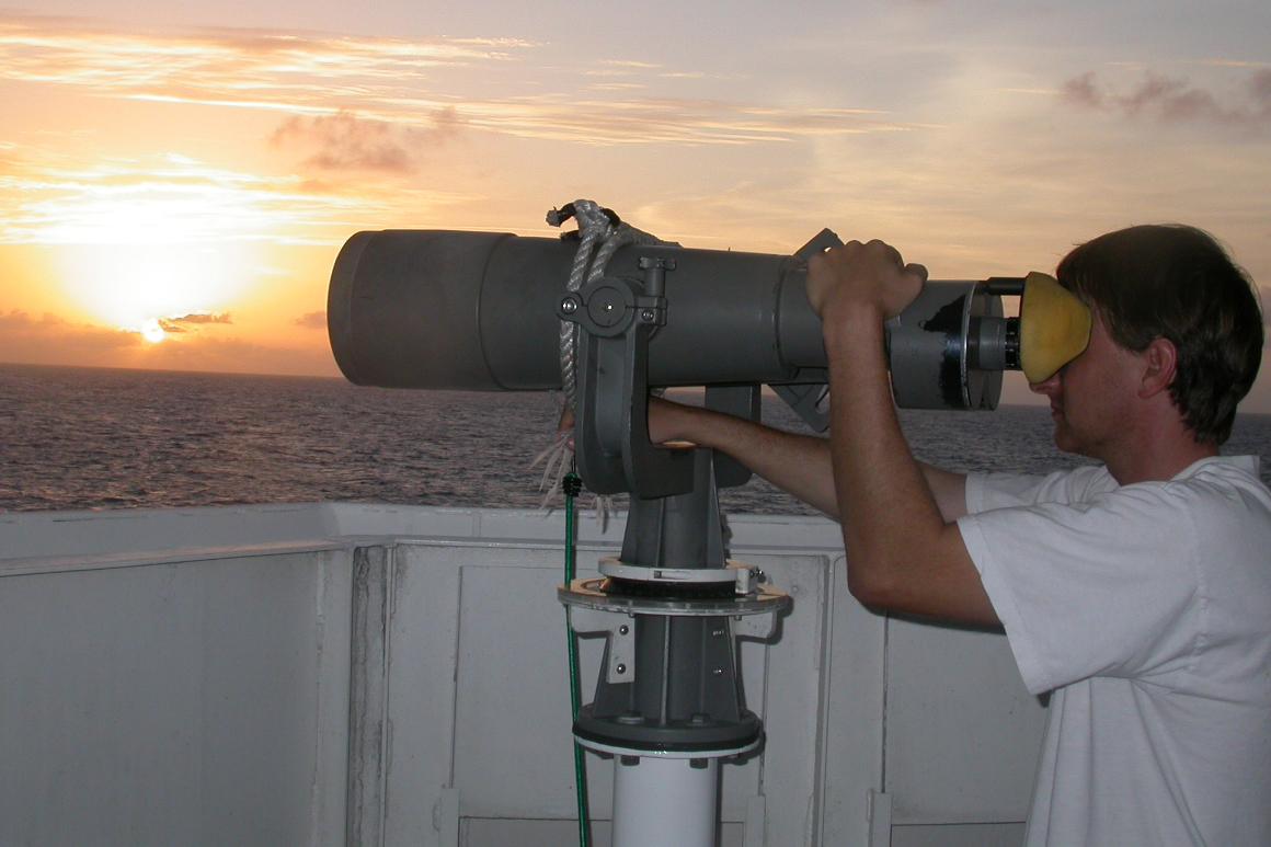 A scientist looking through a large set of binoculars, viewing marine mammals.
