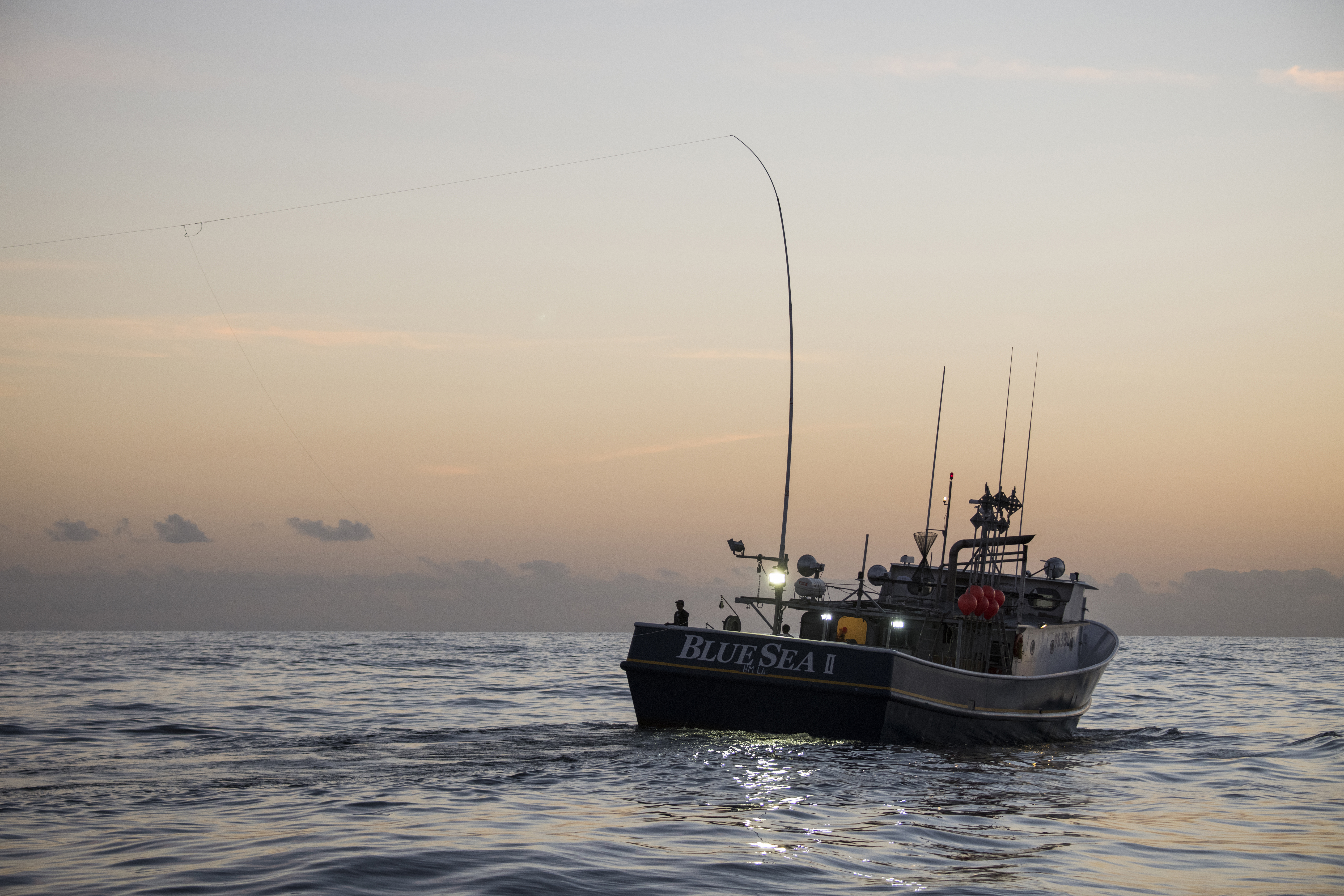 A fishing vessel equipped with Green Stick alternative gear out on the water at dusk.