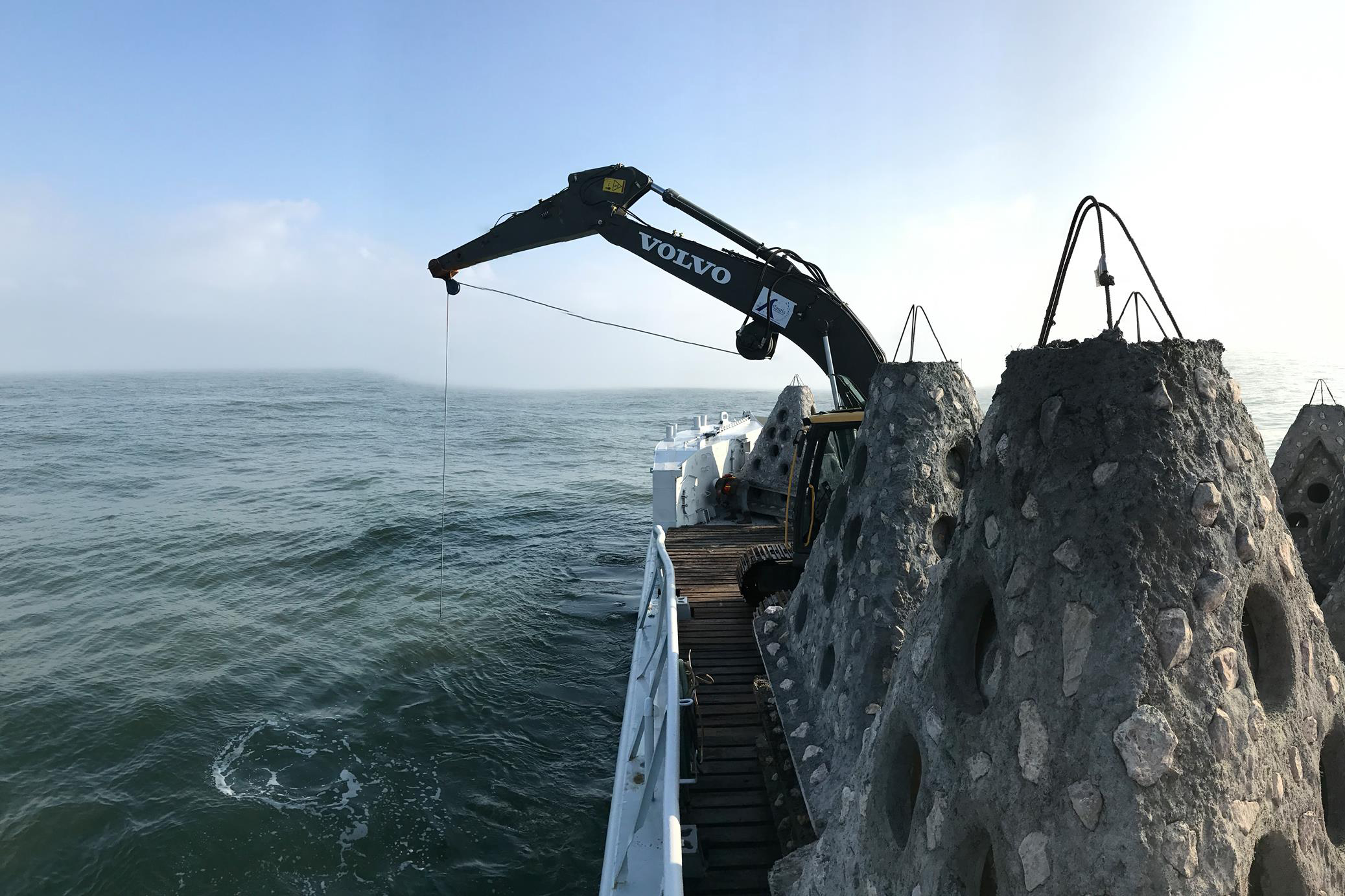 A barge and crane deploy artificial reefs along the Texas Gulf coast.