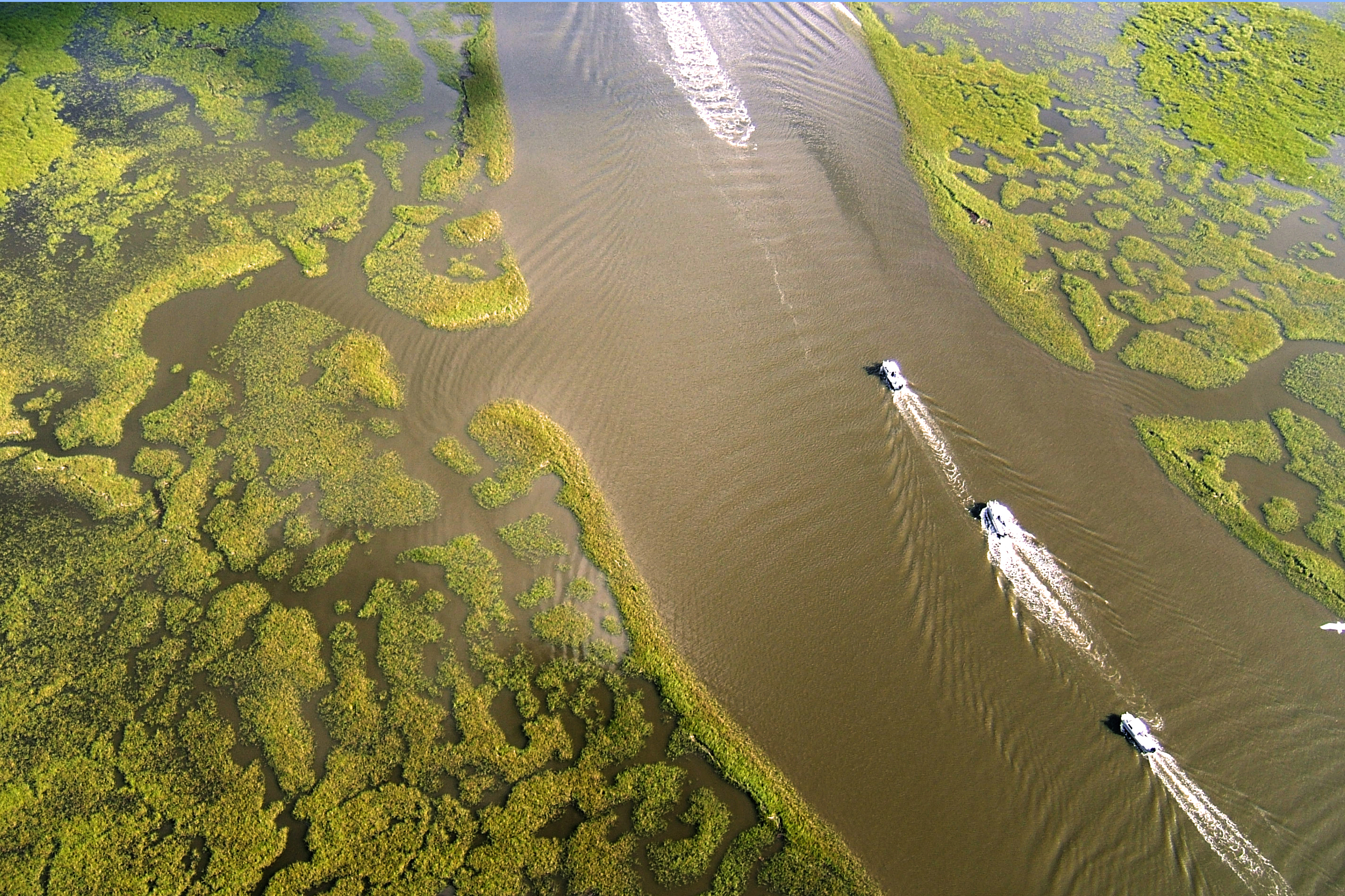 Aerial view of boats traveling along channels surrounded by marsh in Louisiana.