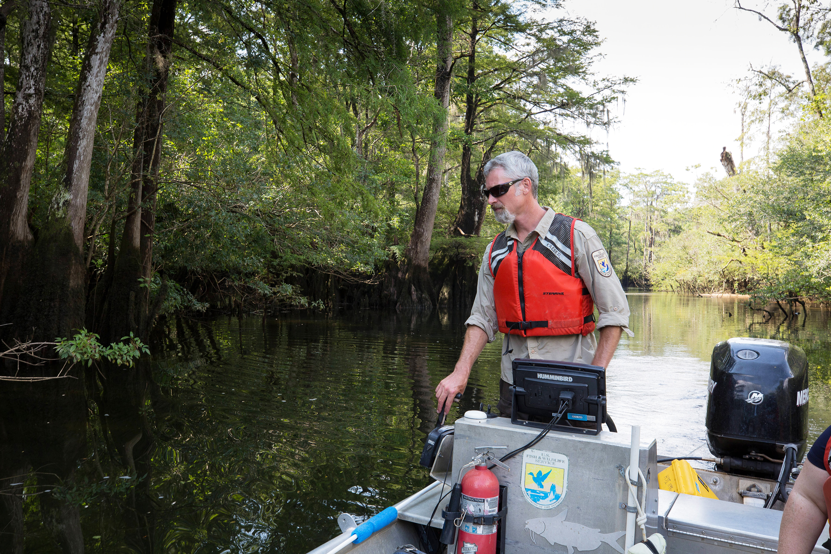 USFWS biologist piloting a boat looking for Gulf Sturgeon in their river habitat.