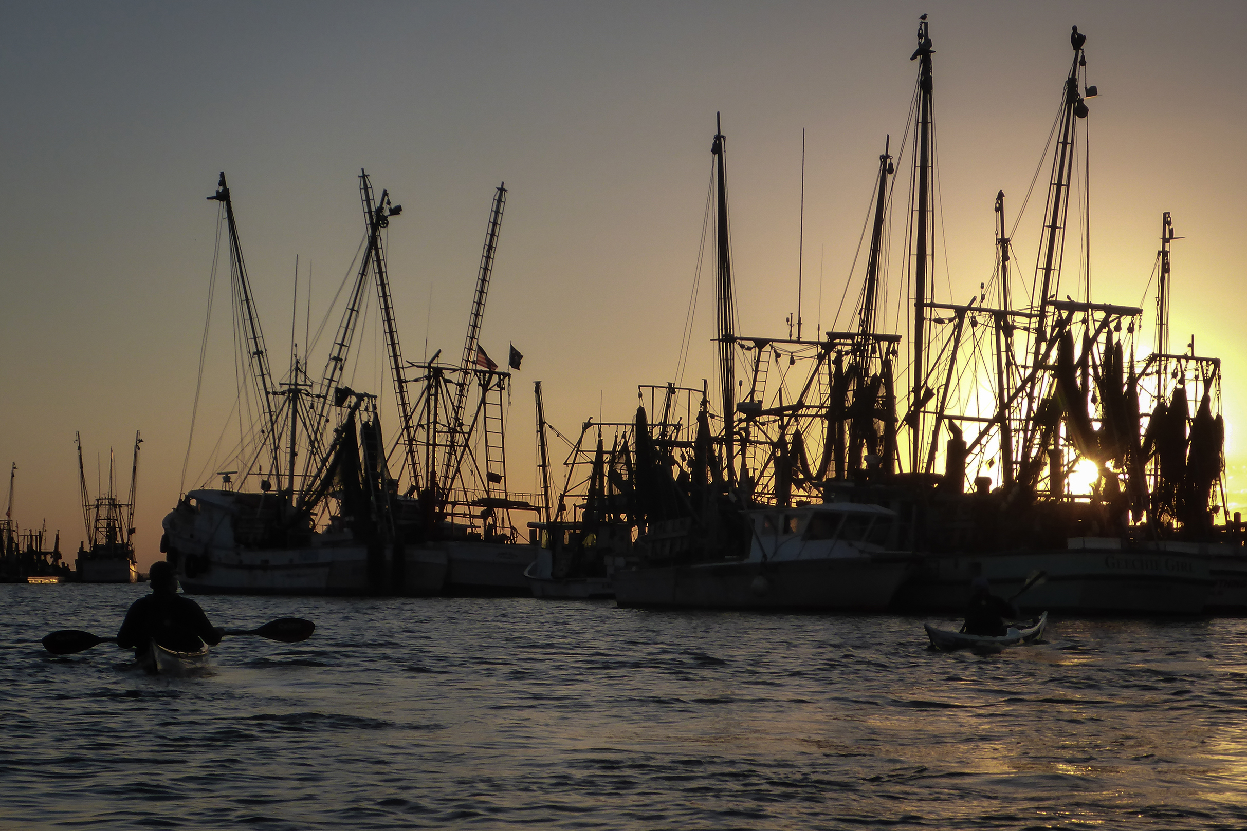 Kayakers paddle around commercial fishing boats at docks as the sun sets.
