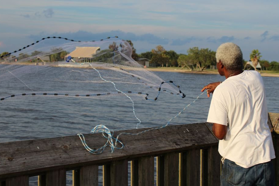 A recreational angler tosses a net out off a fishing pier.