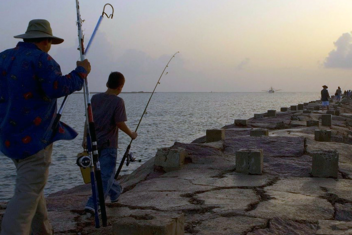 Adult and child holding fishing gear, walking on a pier in Louisiana.