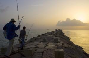 Fishemen walk along a rocky pier.